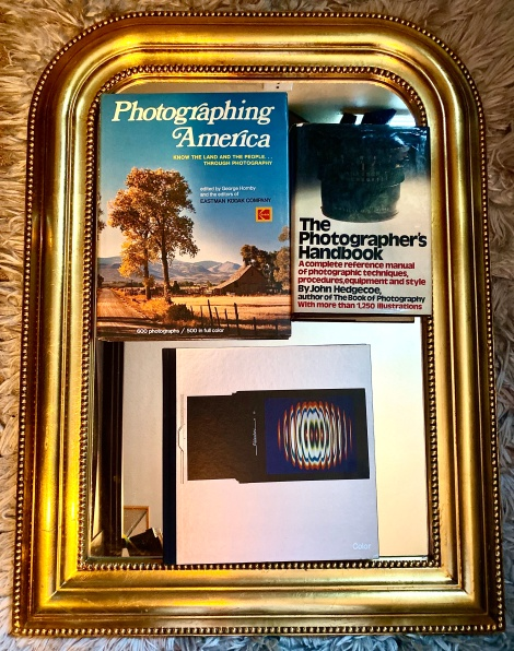 Photographing America by George Hornby and the Editors of Eastman Kodak Company; Color by The Editors of Time-Life Books; The Photographer's Handbook by John Hedgecoe and a gold-framed mirror.